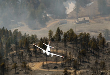 A spotter plane flies low over a smoldering ridge in the Lower North Fork Wildfire burning in the foothills community of Conifer, Colo., southwest of Denver on Tuesday, March 27, 2012. Firefighters are now able to actively battle the blaze on the ground that started on Monday and has already destroyed at least 16 homes in the rugged terrain. (AP Photo/David Zalubowski)