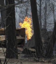 Flames rise from a propane tank near a home destroyed by a wildfire burning in the foothills community of Conifer, Colo., southwest of Denver on Tuesday, March 27, 2012. Firefighters are now able to actively battle the blaze on the ground that started on Monday and has already destroyed at least 23 structures and caused the deaths of two people. (AP Photo/Ed Andrieski, Pool)