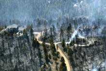 One home stands untouched at left while another home at right smolders after burning in the Lower North Fork Wildfire in the foothills community of Conifer, Colo., southwest of Denver on Tuesday, March 27, 2012. Firefighters are now able to actively battle the blaze on the ground that started on Monday and has already destroyed at least 16 homes in the rugged terrain. (AP Photo/David Zalubowski)