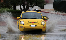 FILE - In this Oct. 17, 2011 file photo, a small car from an extermination company splashes thought a puddle in Miami Beach, Florida's famed South Beach, after flood watch and rip currents were posted in South Florida where storms were expected.  Extreme storms, droughts and heat waves are getting so much worse because global warming that the world has to prepare for an unprecedented onslaught of deadly and costly weather disaster, an international panel of experts says.  (AP Photo/Wilfredo Lee, File)