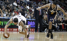New Jersey Nets' Deron Williams, left, loses his balance as Utah Jazz's Devin Harris defends in the fourth quarter of an NBA basketball game, Monday, March 26, 2012, in Newark, N.J. The Jazz won 105-84. (AP Photo/Julio Cortez)