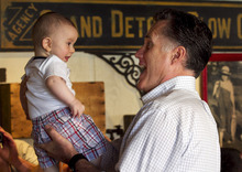 Steven Senne  |  The Associated Press Republican presidential candidate Mitt Romney lifts 8-month-old Gavin Woodford, of Rockford, Ill., during a campaign stop in Rockford on Sunday, March 18.