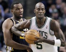 Utah Jazz center Al Jefferson, left, reacts as Boston Celtics forward Kevin Garnett (5) jabs him with an elbow in the second half of an NBA basketball game in Boston, Wednesday, March 28, 2012. The Celtics won 94-82. (AP Photo/Elise Amendola)