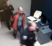 In this image taken from video at the Sanford, Fla., Police Department, George Zimmerman, in red jacket, is escorted into the Sanford police station in handcuffs on Feb. 26, 2012, the night he fatally shot Trayvon Martin. (AP Photo/Sanford Police Department)