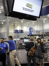Paul Sakuma  |  AP file photo Best Buy workers help customers at a Best Buy in Mountain View, Calif., last year. Best Buy Co. is closing 50 stores in the U.S. in fiscal 2013 and is looking to cut costs by $800 million by fiscal 2015. The biggest U.S. specialty electronics retailer also says it lost money in its fiscal fourth quarter partly because of a restructuring charge, but its adjusted results topped Wall Street's expectations.