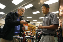 Scott Sommerdorf  |  The Salt Lake Tribune              Uinta Golf salesman Uni Chang helps Larry Ferolie with a club at the 2100 South Uinta store, Thursday, March 29, 2012. A Florida chain of golf shops, Edwin Watts Golf Shops, is buying the five Uinta Golf stores in Utah.