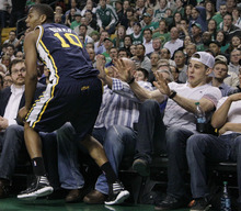 Elise Amendola  |  The Associated Press  Boston Bruins hockey player Tyler Seguin, right, puts his hands up as Utah Jazz guard Alec Burks (10) runs close to the fans to retrieve the ball in the second half of an NBA basketball game against the Boston Celtics in Boston on Wednesday. The Celtics won 94-82.