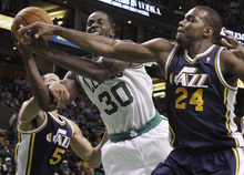 Elise Amendola  |  The Associated Press  Boston Celtics forward Brandon Bass (30) drives between Utah Jazz guard Devin Harris (5) and forward Paul Millsap (24) in the second half of an NBA basketball game in Boston on Wednesday. The Celtics won 94-82.