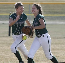 Paul Fraughton | The Salt Lake Tribune.  Olympus softballers, Tina Ford and Haley Tolman celebrate Tolman's  tough catch in the outfield to end the inning in a game against Tooele High School.  Thursday, March 22, 2012