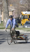 Paul Fraughton | The Salt Lake Tribune Phil Sarnoff, of the Salt Lake Division of Sustainability, rides his bike in Liberty Park, towing a wagon that he uses to carry support materials to promote the City's SmartTrips program. The program held its kickoff event outside Tracy Aviary on Wednesday, March 28, 2012.
