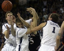 Kim Raff | The Salt Lake Tribune Utah State University players (from left) Danny Berger, Morgan Grim, and Ben Clifford fight for a rebound with Mercer player Bud Thomas during the CIT Championship game at Utah State University in Logan, Utah on March 28, 2012.  Mercer went on to win the game 67-70.