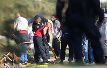 CORRECTS DATE - Relative use shovels after Mohamed Merah's funeral ceremony in a cemetery near Toulouse, southern France, Thursday, March 29, 2012. Mohamed Merah is blamed for a series of deadly shootings which have shocked France and upended the country's presidential race. Merah, who claimed allegiance to al-Qaida, died in a hail of gunfire one week ago after a dramatic 32-hour-long standoff with law enforcement. Algerian authorities said they didn't want to take Mohamed Merah's remains, as his Algerian-born father had wanted. (AP Photo/Marthial Roland)