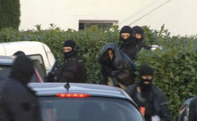 In this image taken from TV, French armed special forces lead away a detained suspect , centre, with covered head, at a location in Nantes, France Friday March 30, 2012.  Police were seen to lead away the man and carry seized items believed to be weapons from the property.  Police have detained 19 people during multiple raids in a crackdown on suspected Islamist extremists in cities around France on Friday, and more such raids are planned, the French president Nicolas Sarkozy said Friday.(AP Photo/I Tele) FRANCE OUT - TV OUT  - NO USE AFTER  30 DAYS FROM FIRST TRANSMISSION