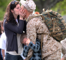 Heather Shuford kisses her husband Capt. Robert Shuford goodbye Monday, March 26, 2012, as their son Aden Shuford, 6, clings to his daddy's arm on Camp Lejeune, Jacksonville, N.C. before Shuford departed on deployment with the 24th Marine Expeditionary Unit. (AP Photo/The Daily News, John Althouse)