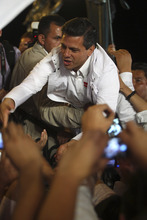 Mexican presidential candidate Enrique Pena Nieto, of the Revolutionary Institutional Party, PRI, reaches out to greet supporters as he is supported by a body guard, during his official campaign kickoff in Guadalajara, Mexico, early Friday March 30, 2012. Nieto starts the 90-day campaign, set by electoral law, with more than a 10-point lead in most polls over his closet opponent, Josefina Vazquez Mota of the now-governing National Action Party. Mexico will hold general elections on July 1. (AP Photo/Bruno Gonzalez)