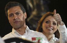 Mexican presidential candidate Enrique Pena Nieto, of the Revolutionary Institutional Party, PRI, officially launches his campaign as his wife Angelica Rivero, flashes a thumbs up from behind him, in Guadalajara, Mexico, early Friday March 30, 2012. Nieto starts the 90-day campaign, set by electoral law, with more than a 10-point lead in most polls over his closet opponent, Josefina Vazquez Mota of the now-governing National Action Party. Mexico will hold general elections on July 1. (AP Photo/Bruno Gonzalez)