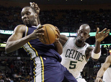 Utah Jazz center Al Jefferson, left, spins to the basket against the defense of Boston Celtics forward Kevin Garnett (5) in the first half of an NBA basketball game in Boston, Wednesday, March 28, 2012. (AP Photo/Elise Amendola)