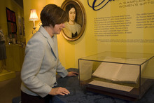 Julie Beck, president of the general Relief Society, looks at the minute book kept by the first Relief Society. Courtsesy of the LDS Church