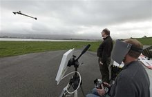 In this March, 28, 2012, photo, Andreas Oesterer, right, uses a video link to fly a Ritewing Zephyr II drone at a waterfront park as Mark Harrison, left, watches in Berkeley, Calif.Interest in the domestic use of drones is surging among public agencies and private citizens alike, including a thriving subculture of amateur hobbyists, even as the prospect of countless tiny but powerful eyes circling in the skies raises serious privacy concerns. (AP Photo/Eric Risberg)