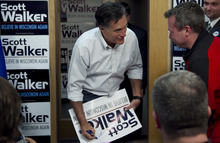 Republican presidential candidate, former Massachusetts Gov. Mitt Romney signs placards for supporters of Wisconsin Republican Gov. Scott Walker at a phone bank during a campaign stop in Fitchburg, Wis., Saturday, March 31, 2012.  The phone bank is used in support of Walker who is facing a recall election in June 2012. (AP Photo/Steven Senne)