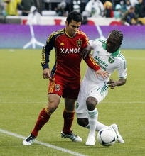 Real Salt Lake defender Tony Beltran, left, battles for the ball with Portland Timbers midfielder Diego Chara during the first half of their MLS soccer game  in Portland, Ore., Saturday, March 31, 2012.(AP Photo/Don Ryan)