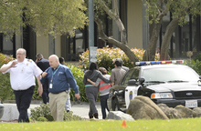 An unidentified group leaves Oikos University after a school shooting in Oakland, Calif., Monday, April 2, 2012. A suspect was detained Monday in a shooting attack at a California Christian university. (AP Photo/Noah Berger)