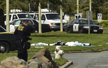 Bodies lie covered on the grass as Oakland Police work near Oikos University in Oakland, Calif., Monday, April 2, 2012. A suspect was detained Monday in a shooting attack at a California Christian university that sources said has left at least five people dead. (AP Photo/Noah Berger)
