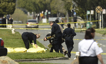 Oakland Police cover bodies near Oikos University in Oakland, Calif., Monday, April 2, 2012. A gunman opened fire at Oikos University in California Monday, killing at least five people, law enforcement sources close to the investigation said. Police say they have a suspect in custody. (AP Photo/Noah Berger)