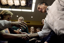 Republican presidential candidate, former Massachusetts Gov. Mitt Romney,right, greets people in an overflow room at a town-hall style campaign event in, Madison, Wis., Sunday, April 1, 2012. (AP Photo/Steven Senne)