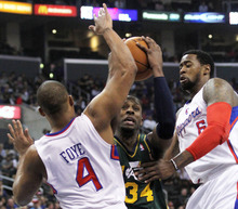 Utah Jazz's guard C.J. Miles, center, drives between Los Angeles Clippers' guard Randy Foye, left, and center DeAndre Jordan, right, during the first half of a NBA basketball game in Los Angeles, Saturday, March 31, 2012.  (AP Photo/Ringo H.W. Chiu)