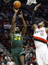 Utah Jazz forward Paul Milsap, left, shoots against Portland Trail Blazers forward LaMarcus Aldridge during the first quarter of their NBA basketball game in Portland, Ore., Monday, April 2, 2012. (AP Photo/Don Ryan)