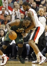 Utah Jazz center Al Jefferson, left, drives on Portland Trail Blazers forward LaMarcus Aldridge during the second half of their NBA basketball game in Portland, Ore., Monday, April 2, 2012.  Jefferson scored 20 points and pulled in ten rebounds as they beat the Blazers 102-97. (AP Photo/Don Ryan)