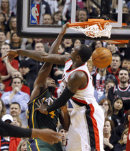 Utah Jazz forward Paul Milsap, left, scores against Portland Trail Blazers forward J.J. Hickson during the second half of an NBA basketball game in Portland, Ore., Monday, April 2, 2012. Milsap led Utah in scoring with 31 points as the Jazz beat the Blazers 102-97. (AP Photo/Don Ryan)