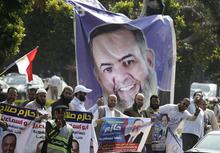 FILE - In this Friday, March 30, 2012 file photo, supporters of Egyptian presidential candidate Hazem Salah Abu Ismail, a prominent Salafi, celebrate in front of a giant campaign banner at the Higher Presidential Elections Commission, in Cairo, Egypt. Trying to unite divided Islamists behind him, the presidential hopeful of Egypt's Muslim Brotherhood has promised to give religious clerics power to review legislation to ensure it is in line with Islamic law, a group of ultraconservative Muslim clerics said Wednesday. Brotherhood candidate Khairat el-Shater is trying to avert a split in the votes of religious conservatives in next month's presidential election. The Brotherhood is Egypt's strongest fundamentalist group, but several other Islamists are running in the vote _ particularly Hazem Abu Ismail, who has strong support among Salafis, the most hard-line religious movement in Egypt. (AP Photo/Amr Nabil, File)