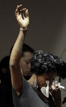 A woman raises her arm as she weeps during a memorial service at the Allen Temple Baptist Church Tuesday, April 3, 2012, in Oakland, Calif.Several hundred people gathered Tuesday night for a prayer vigil for the victims of Monday's shooting at Oikos University, a small Christian school in Oakland. (AP Photo/Ben Margot)