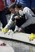 Francisco Kjolseth  |  The Salt Lake Tribune Placing flowers, Brian Hoopes of Taylorsville stays close his son Patrick, 3, who is tethered to him for his intravenous fluids since he was essentially born without intestines. On Wednesday, April 4, 2012, Patrick ceremoniously started the Celebration of Life Monument fountain on Library Square in Salt Lake which is dedicated to those who have given the gift of life through organ, eye, tissue and blood donation. Patrick has been on the donor list for a small intestine for three years.