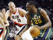 Utah Jazz center Al Jefferson, right, drives to the basket against Portland Trail Blazers center Joel Przybilla during the first quarter of their NBA basketball game in Portland, Ore., Monday, April 2, 2012. (AP Photo/Don Ryan)