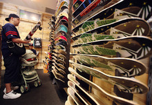 Lennie Mahler  |  The Salt Lake Tribune Gennin Lewis browses the skateboard decks at Epic Boardshop inside the Gateway Mall in Salt Lake City, Wednesday, April 4, 2012. The shop recently opened in a location previously occupied by Gymboree, which is now located at City Creek Center.