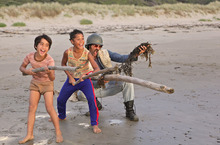 Brothers Rocky (Te Aho Aho Eketone-Whitu) and Boy (James Rolleston) play on the beach with their dad (Taika Waititi) in