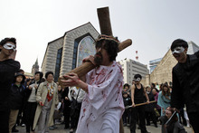 A South Korean Christian devotee carries a cross while reenacting Jesus' path to his crucifixion during a performance for the Easter in Seoul, South Korea, Sunday, April 8, 2012. Easter Sunday caps a week of holidays that commemorate the crucifixion and return to life of Jesus. (AP Photo/Lee Jin-man)