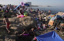 Filipinos enjoy a picnic as others swim at the polluted waters of Manila's bay, Philippines as they celebrate Easter Sunday, April 8, 2012. Despite a city-imposed swimming ban, many Filipinos set up makeshift tents and swam along the bay to cool themselves from summer's sweltering heat. (AP Photo/Aaron Favila)
