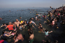 Filipinos swim at the polluted waters of Manila's bay, Philippines as they celebrate Easter Sunday, April 8, 2012. Despite a city-imposed swimming ban, many Filipinos set up makeshift tents and swam along the bay to cool themselves from summer's sweltering heat. (AP Photo/Aaron Favila)