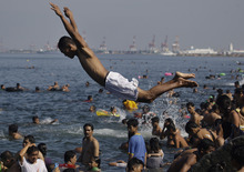 A Filipino dives at the polluted waters of Manila's bay, Philippines as they celebrate Easter Sunday, April 8, 2012. Despite a city-imposed swimming ban, many Filipinos set up makeshift tents and swam along the bay to cool themselves from summer's sweltering heat. (AP Photo/Aaron Favila)
