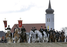 Men of the Sorbian community ride on decorated horses during the traditional Easter procession in Ralbitz, 70km (45miles) east of Dresden, Germany, Sunday, April 8, 2012. Sorbian men wearing black coats and top hats, sing holy songs on horseback and preach the message of Jesus' resurrection. The Sorbs are a Slavic, Catholic minority group in eastern Germany. (AP Photo/Gero Breloer)