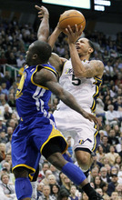 Utah Jazz point guard Devin Harris (5) attempts to score against Golden State Warriors point guard Nate Robinson, left, during the second half of an NBA basketball game, Friday, April 6, 2012, in Salt Lake City. The Jazz defeated the Warriors 104-98. (AP Photo/Colin E Braley)