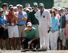 Graeme McDowell, of Northern Ireland, plans his shot out of the rough off the first fairway with caddie Ken Comboy during the fourth round of the Masters golf tournament Sunday, April 8, 2012, in Augusta, Ga. (AP Photo/David J. Phillip)