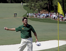 Louis Oosthuizen, of South Africa, throws his ball to a spectator after hitting an eagle two on the par 5 second hole during the fourth round of the Masters golf tournament Sunday, April 8, 2012, in Augusta, Ga. (AP Photo/Matt Slocum)