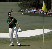 Louis Oosthuizen, of South Africa, throws his ball to a spectator after hitting adouble eagle two on the par 5 second hole during the fourth round of the Masters golf tournament Sunday, April 8, 2012, in Augusta, Ga. (AP Photo/Matt Slocum)