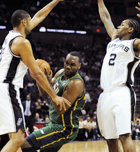 Utah Jazz's Al Jefferson, center, is defended by San Antonio Spurs' Tim Duncan, left, and Kawhi Leonard during the first half of an NBA basketball game, Sunday, April 8, 2012, in San Antonio. (AP Photo/Darren Abate)