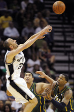 San Antonio Spurs' Manu Ginobili, left, of Argentina, shoots over Utah Jazz's C.J. Miles, right, and Enes Kanter during the first half of an NBA basketball game, Sunday, April 8, 2012, in San Antonio. (AP Photo/Darren Abate)